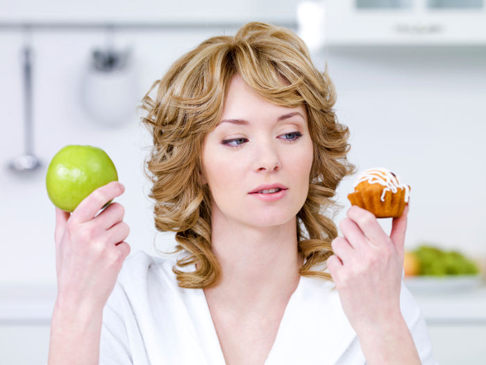 Young beautiful woman choose between sweet cake and green apple - in the kitchen